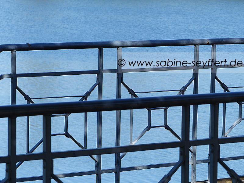 Geländer am See mit blauem Wasser